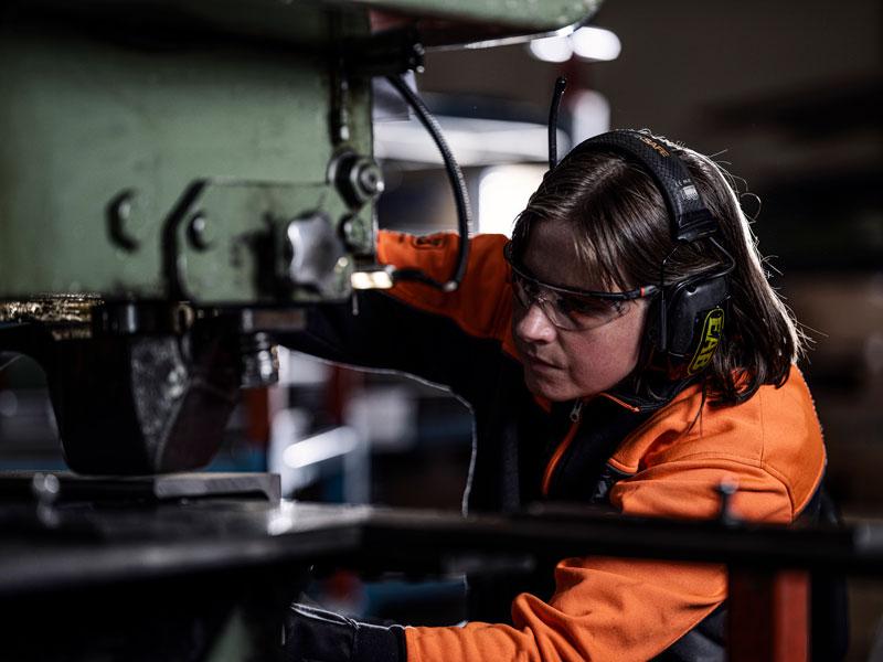 Kvinna fixar vid maskin lagerinredningar