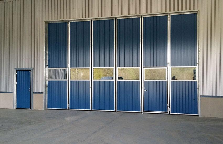 Blå vikportar med en rad glas och gångdörr vid sidan